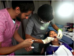 Isai Ramirez (right) assists a dentist during his mission trip to the Philippines.