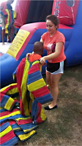 Stephanie Guerrero assist a KAES student with his sumo attire.
