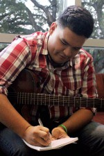 Josh writes down the words to a new song for his group.