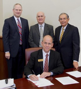 From left: Jeff Bromme, Adventist Health System senior vice president and chief legal officer and member of Southwestern's Board of Trustees; Larry Moore, board chairman; Max Trevino, board member emeritus; and Ken Shaw, University president. Shaw is shown signing the document during the recent Board of Trustees meeting.