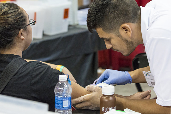 David Hernandez, Southwestern, senior nursing major, draws blood from a patient during the three-day Pathways to Health event in San Antonio.