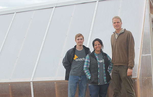 Tony Seery (Enactus President 2014-2015), Ana Patterson (faculty advisor) and Alex Froom (Rez Refuge Executive Director) stand in front of completed greenhouse. Enactus took the lead in constructing the greenhouse during last year's trip.