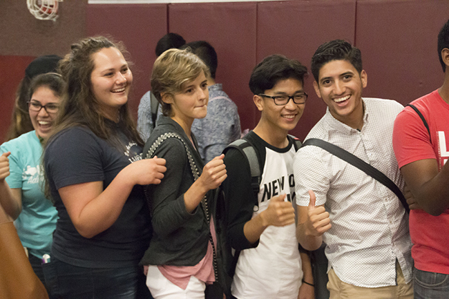 Students eagerly wait their chance to bump fists with other students in the gym on Aug. 25.