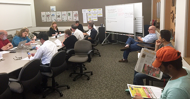 Jordan Greene and Herman Aguilar (far right) sit in on the editors' meeting at the Dallas Morning News last Thursday.